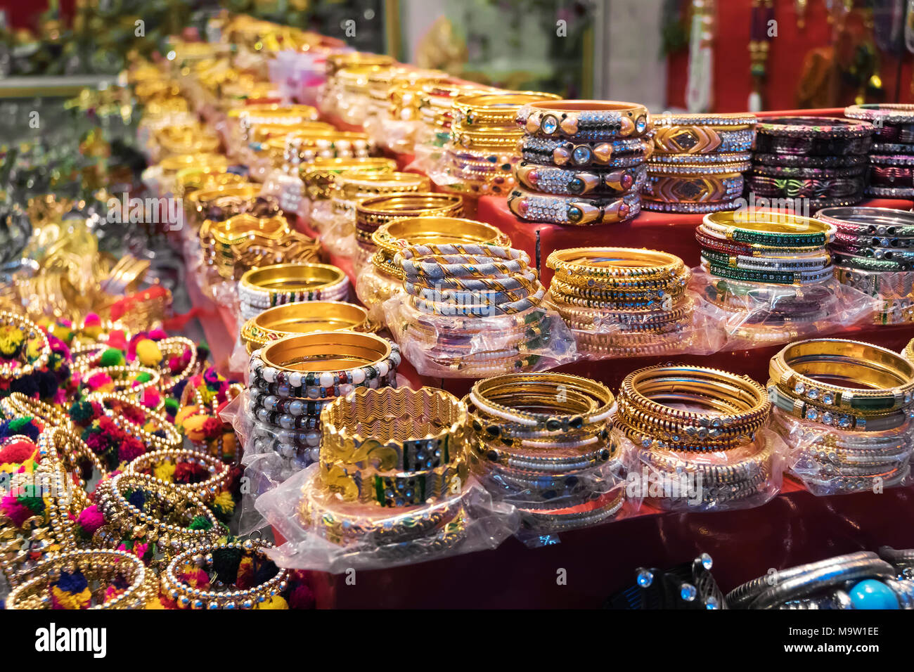 Bright colorful Tibetan traditional bracelets for sale on the street market. beautiful shiny charm bracelets and costume jewelry in Indian style - Stock Image