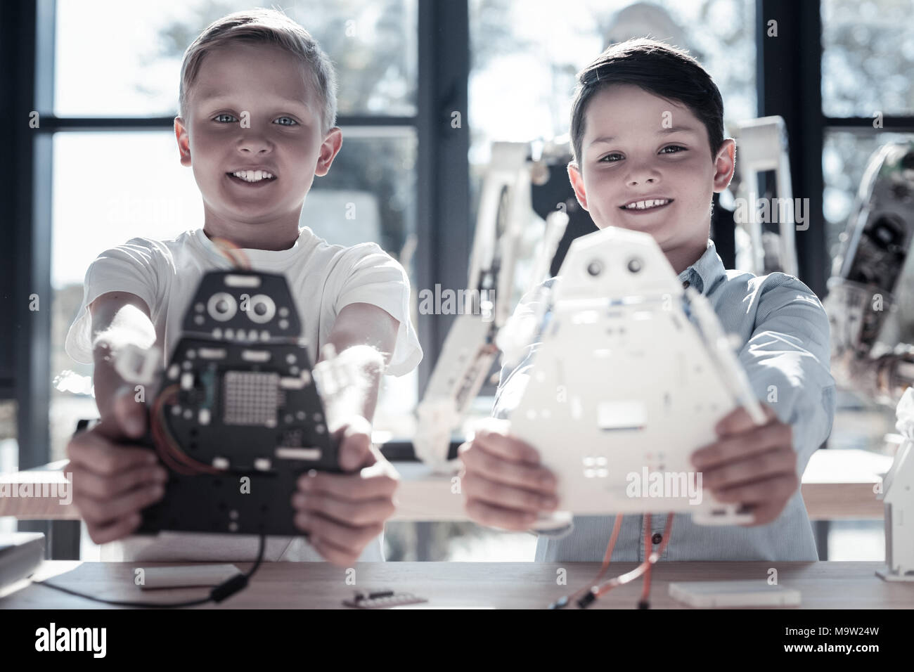 Satisfied preteen boys showing their robotic machines - Stock Image