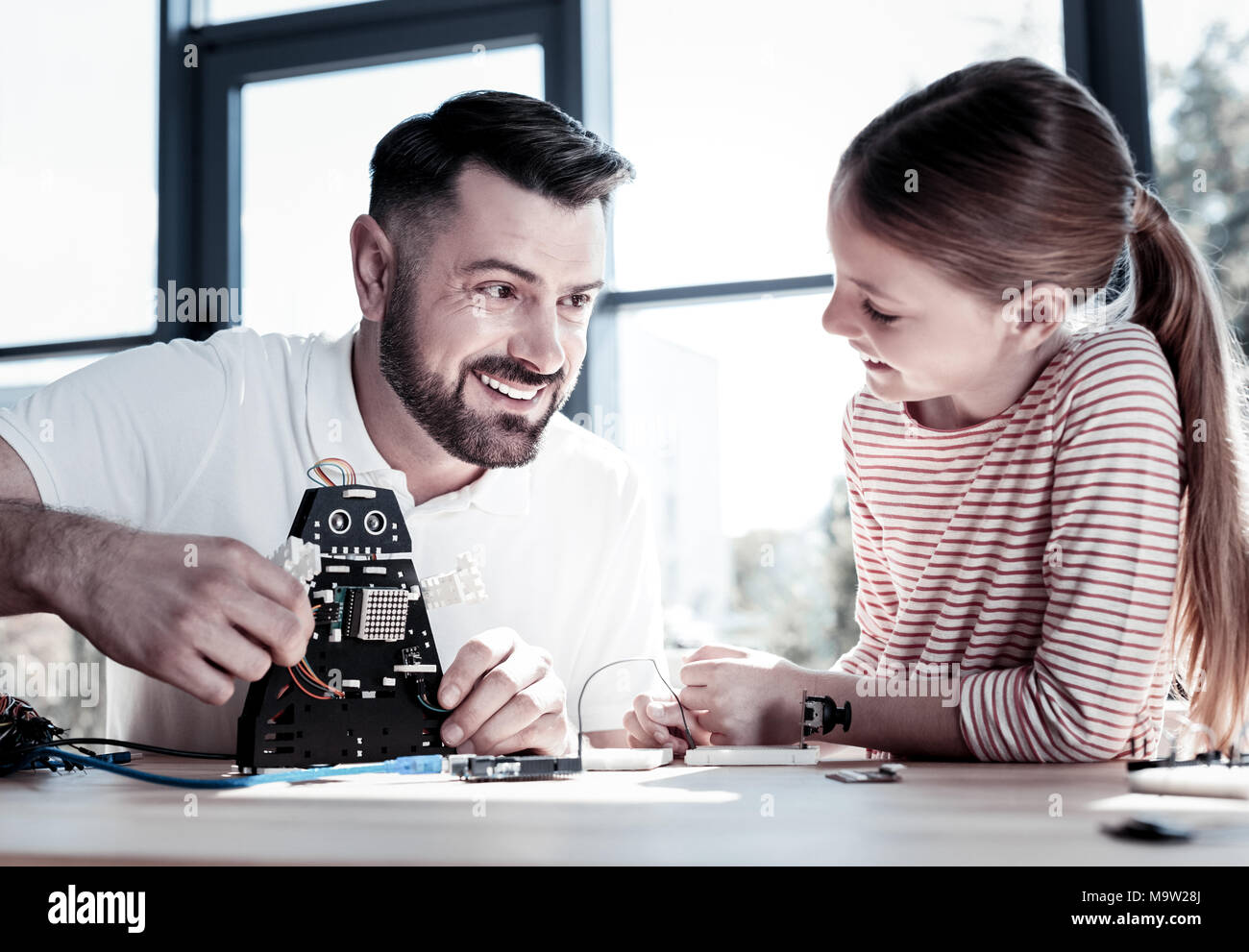 Adorable father and daughter designing robotic machine together - Stock Image