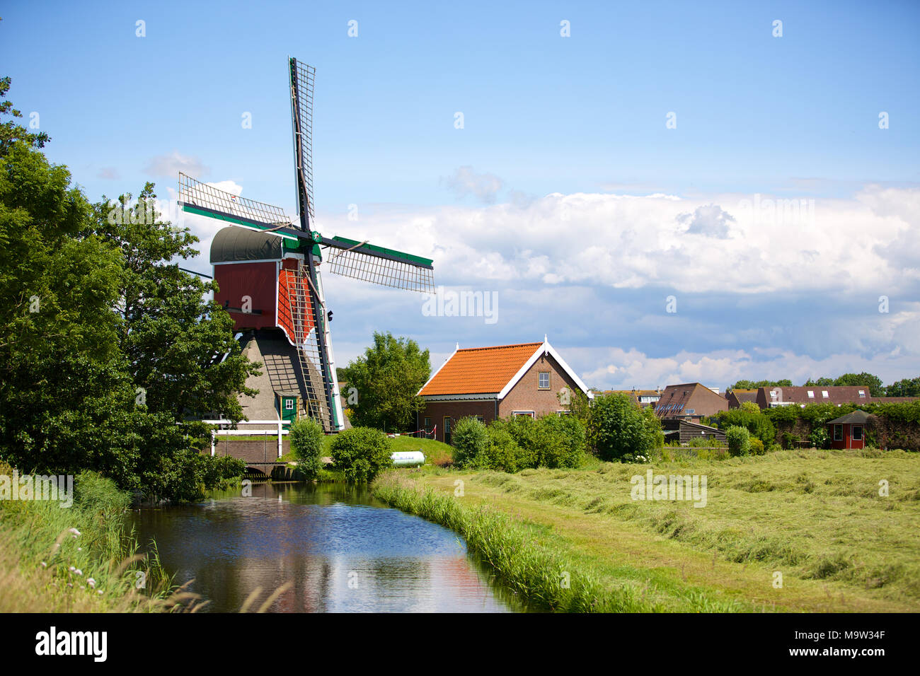 A historical water windmill on a little river and freshly mown grassland in Oud Ade in the Netherlands. - Stock Image