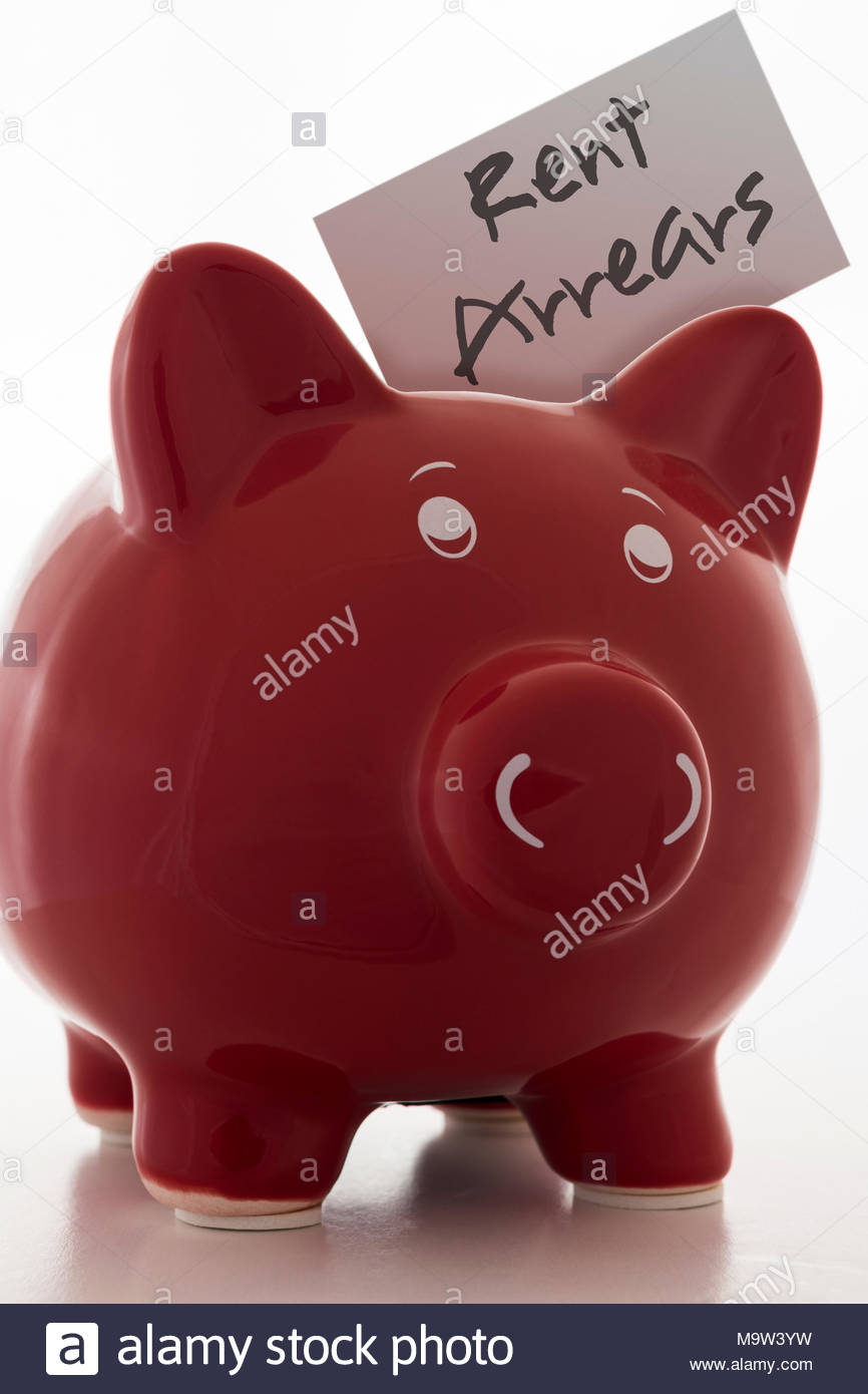 Red Piggy Bank (Money Box) with the label Rent Arrears - Stock Image