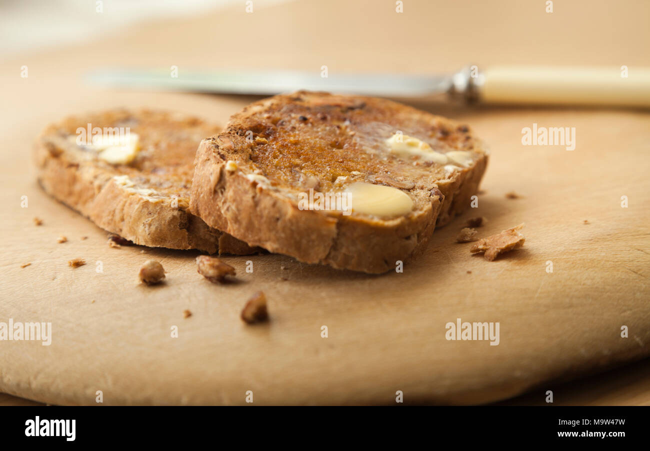 Two slices of warm nutty artisan bread toasted with melting butter on wooden board with a knife out of focus beside the slices. - Stock Image