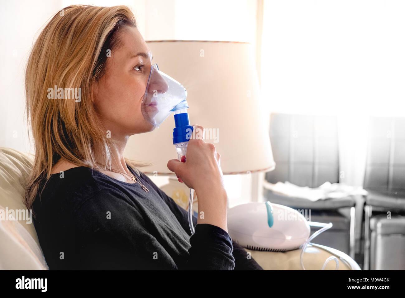 nebulizer aerosol woman inhaler machine medicine at home - Stock Image