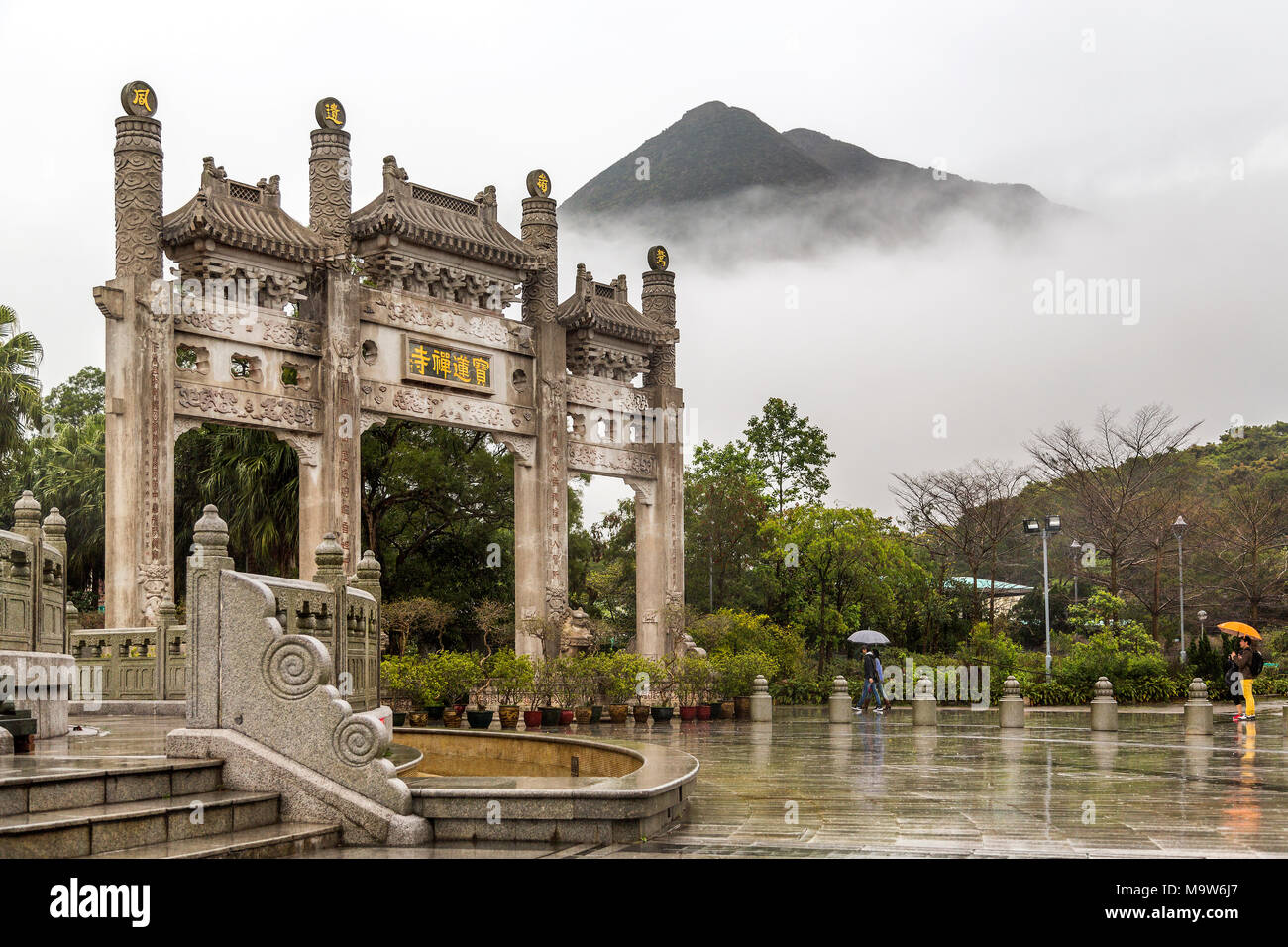 Po Lin Monastery Gate with the mist obscuring the mountain beyond. Located at Ngong Ping, Lantau Island, one of the Hong Kong Islands. Stock Photo