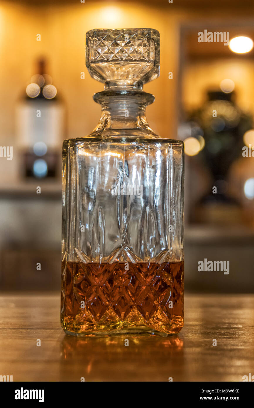 Antique whiskey bottle on top of bar counter. - Stock Image