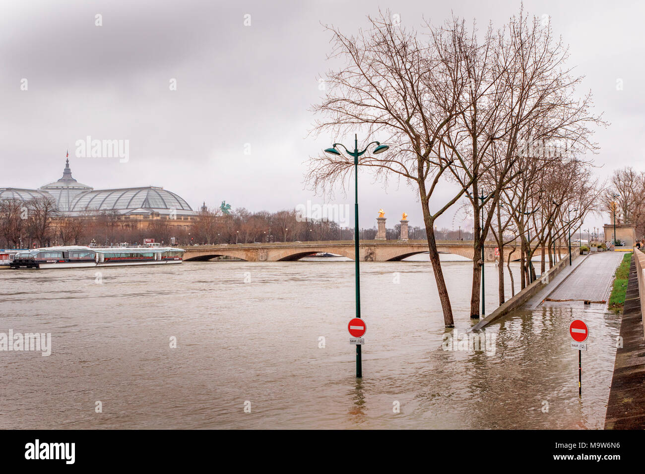 Pont des Invalides submerged in high river Seine during the Paris flood of January 2018, with flooded embankment, submerged trees, signs and lamp post - Stock Image