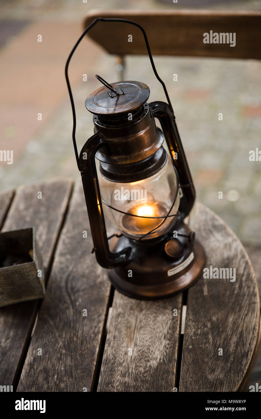 Oil lamp on a wooden round table surface - Stock Image