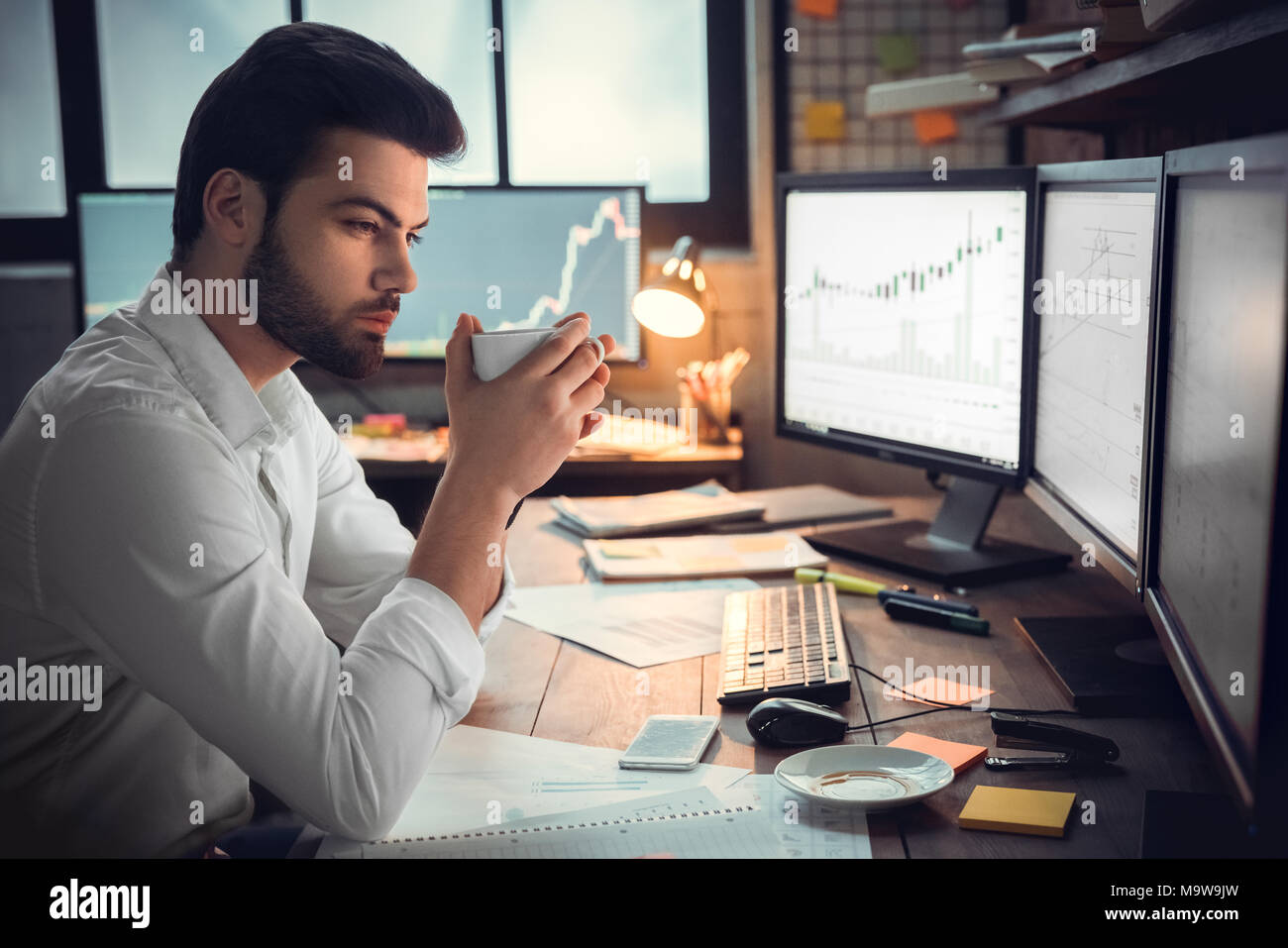 Thoughtful serious trader broker drinking coffee working overtime looking at computer monitors analyzing stock trading market graphs, overwork, lack o - Stock Image