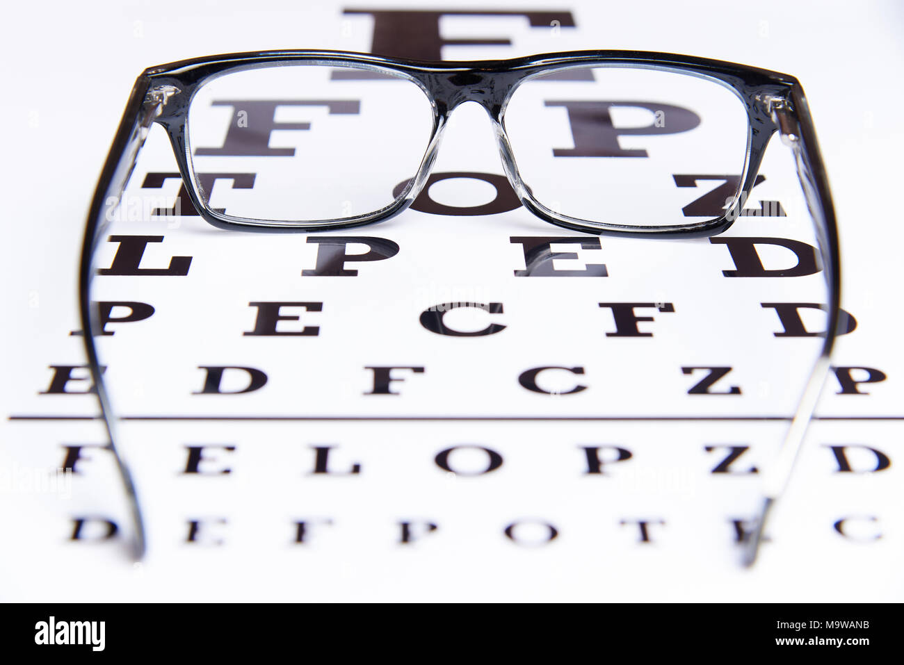 Eye exam chart blurred stock photos eye exam chart blurred stock glasses lie on the table for eye examination stock image geenschuldenfo Gallery