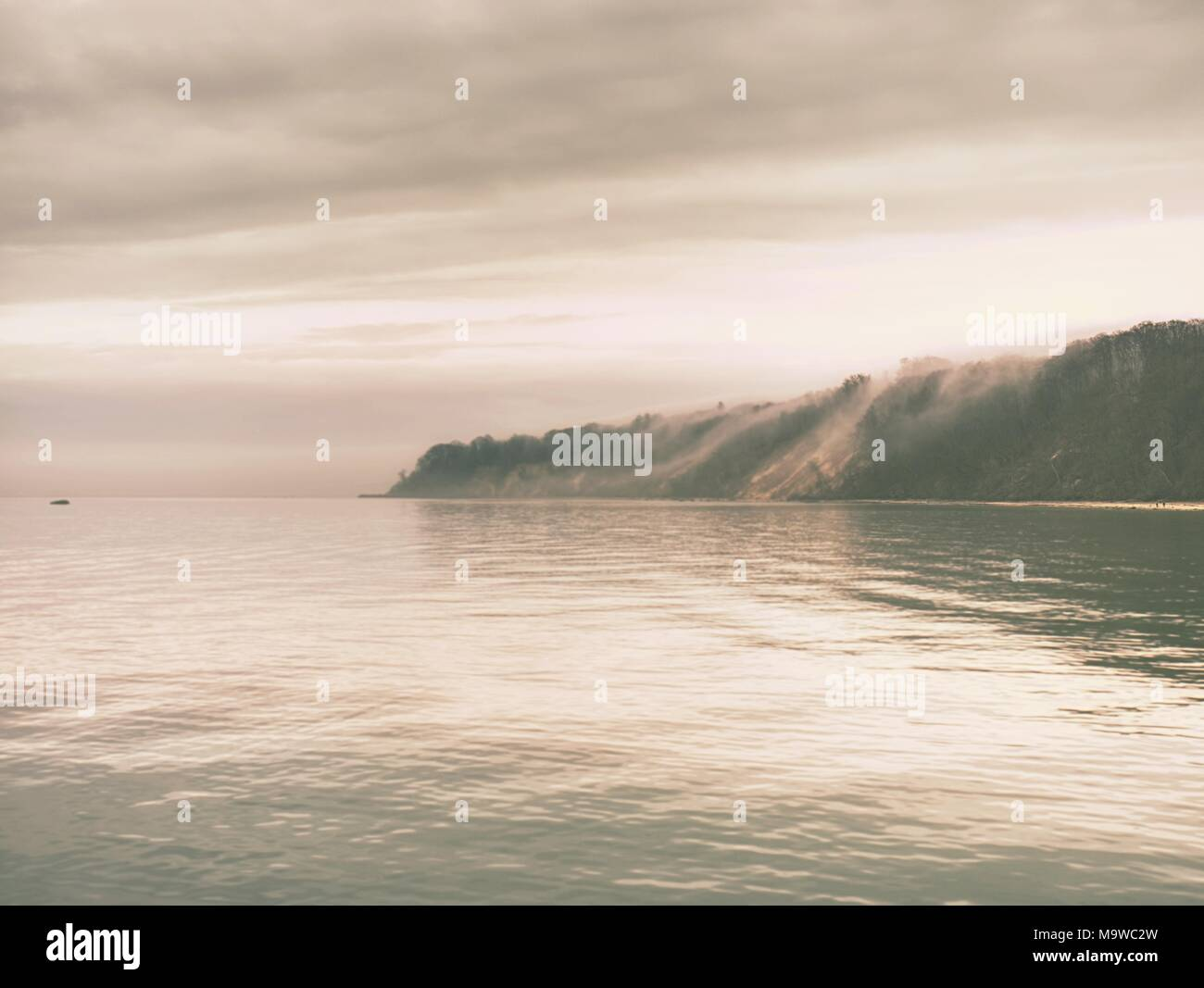 Beautiful sunset in the sea.  Low clouds, countour of landscape lost in mist. Warm colors. - Stock Image