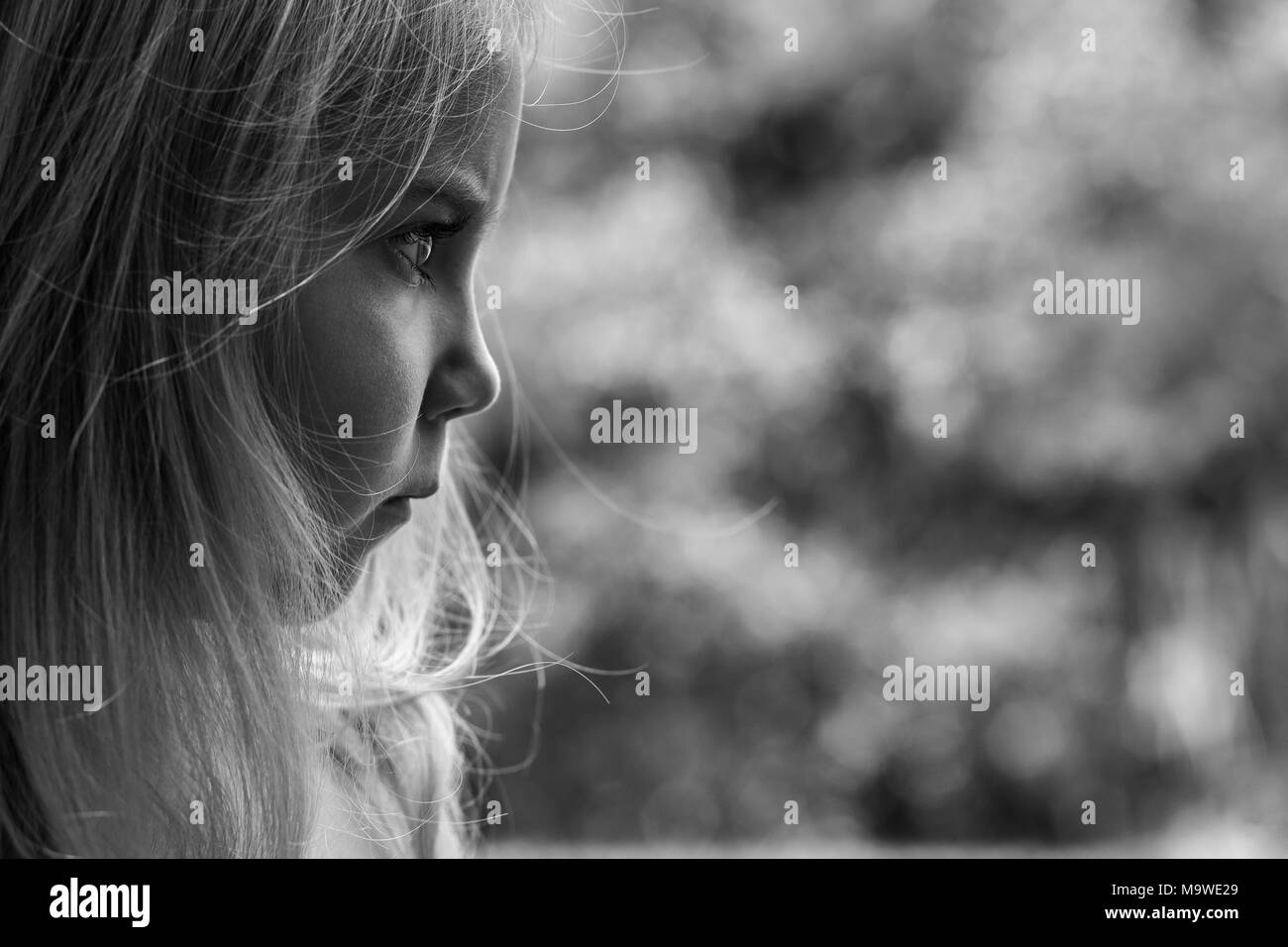 Black and white close up of a little girl looking frustrated - Stock Image