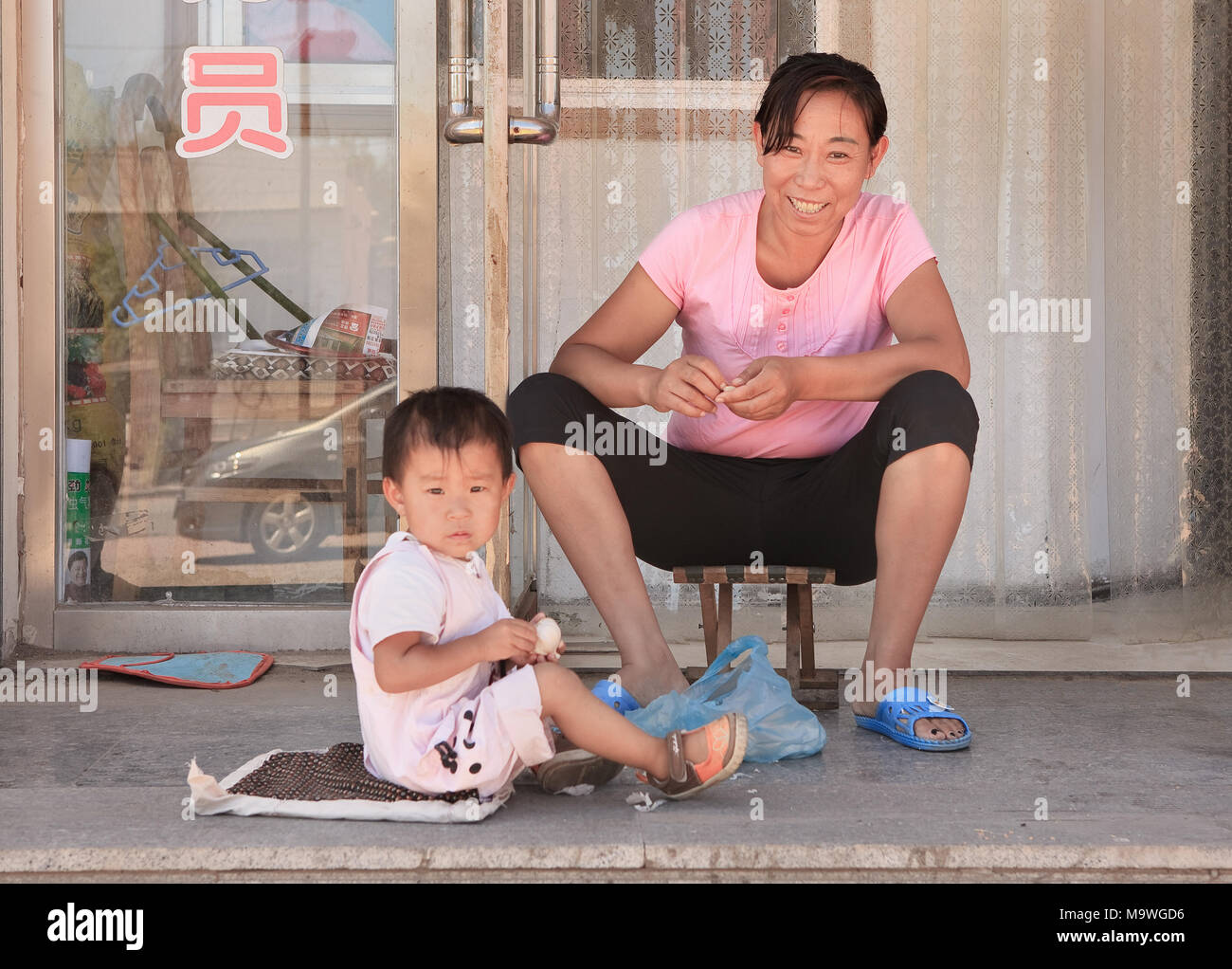 BEIJING-AUGUST 16, 2010. Woman with child in front of house. China has ended the one-child policy after 35 years, allow couples having two children. - Stock Image