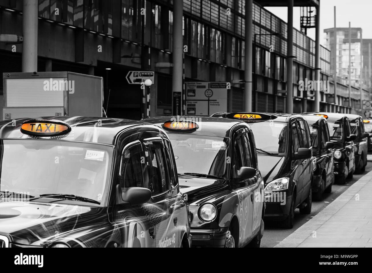A queue of London black cab taxis in a row at a taxi rank, waiting to pick up passengers near Kings Cross station with for hire light illuminated Stock Photo