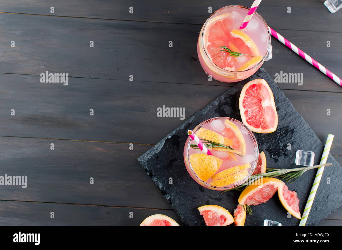 Cocktail with grapefruit slices and ice, ingredients for a drink on dark wooden table, copy space - Stock Image