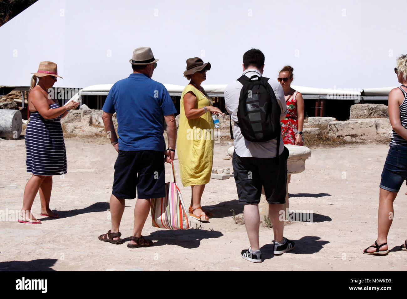 A FEMALE GUIDE LEADING A TOURIST GROUP WITHIN THE ANCIENT RUINS OF SALAMIS. NORTHERN CYPRUS - Stock Image