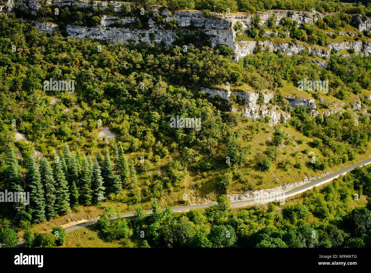 A road cuts through the limestone landscape of the Lot region in south west France. - Stock Image