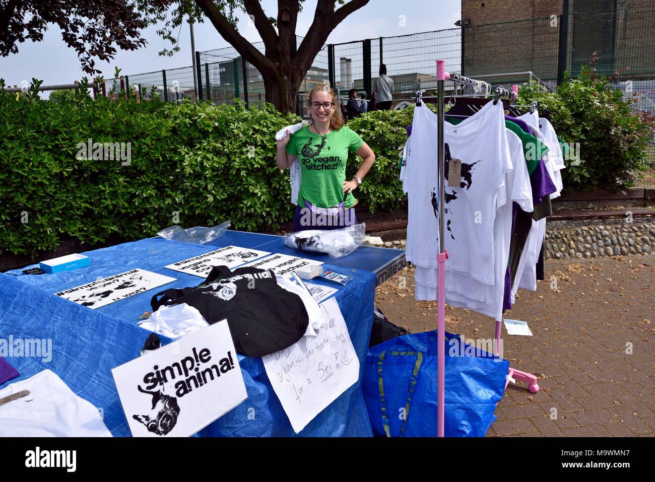 Woman selling Go Vegan tee shirts from stall at vegan festival Calthorpe Project, Greys Inn Road, London Borough of Camden, England Britain Uk - Stock Image