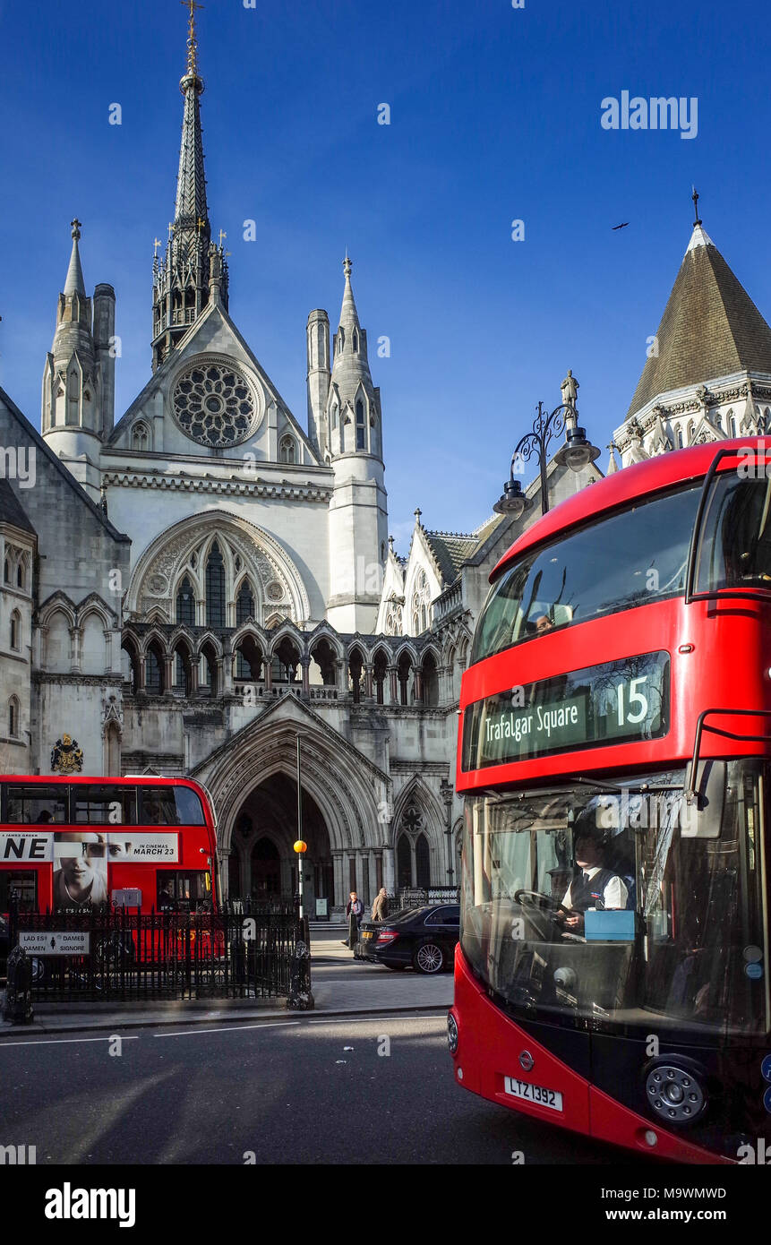 Buses pass the Royal Courts of Justice on the Strand in London. The building commonly known as the Law Courts houses the High Court & Court of Appeal. - Stock Image