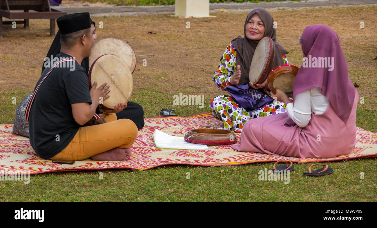 One Malay man wearing a sonkok and three women wearing hijabs are sitting on a traditional rattan mat and playing the kompang (Malay drum). - Stock Image