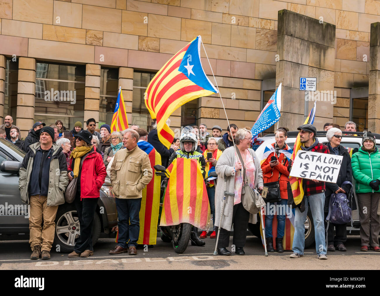 Edinburgh, Scotland, United Kingdom, 28th March 2018. Demonstrators and supporters of Professor Clara Ponsati waving Catalan flags outside Edinburgh Sheriff Court, Chambers Street, as Clara Ponsati, former Catalan Education Minister, appears in an initial extradition court hearing. Demonstrators included Scottish independence supporters. A male protestor holds a placard reading 'Catalona is not Spain'. A motorcyclist with a Catalonian flag draped over the motorcycle - Stock Image