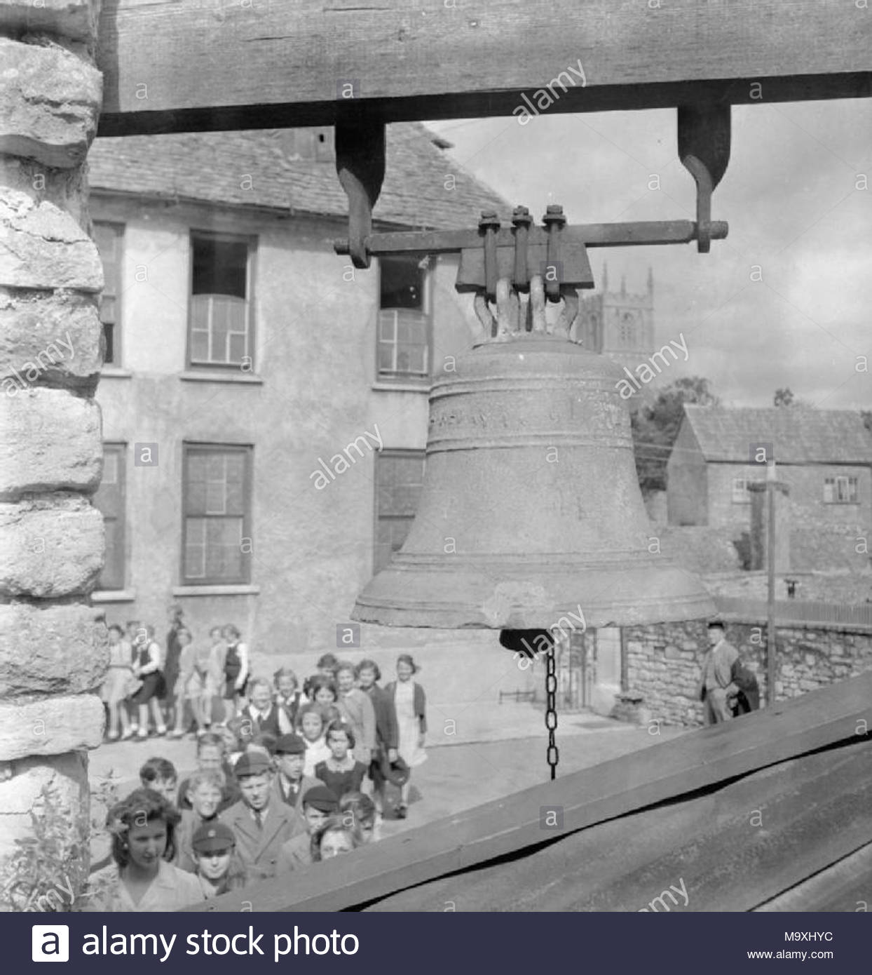 Local Government in a Country Town- Everyday Life in Wotton-under-edge, Gloucestershire, England, UK, 1944 Children file from one class to another across the playground of Katharine Lady Berkeley's Grammar School in Wotton-under-Edge. The photograph is taken looking past the bell which calls the children to class. The bell was presented to the school in 1626 by the Countess of Warwick. In the background can be seen the tower of the Church of St Mary the Virgin. - Stock Image