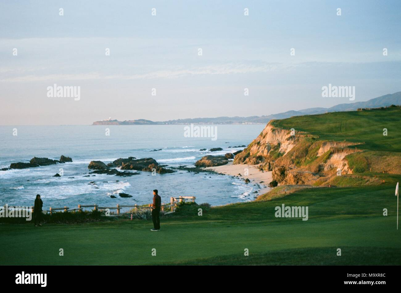 People stand along the greens of the Half Moon Bay Golf Links, a golf course in Half Moon Bay, California, at sunset, December 22, 2017. () - Stock Image