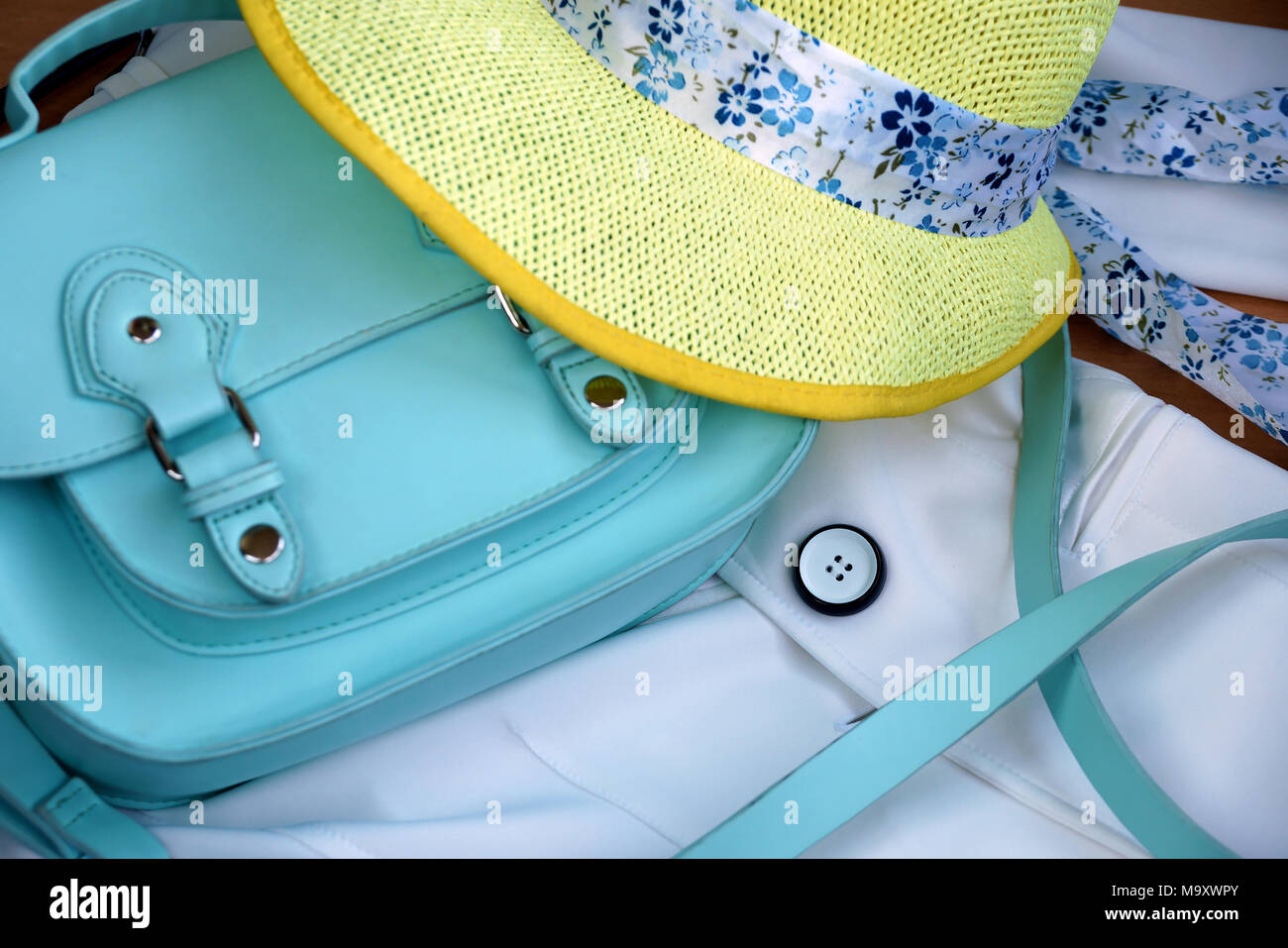 Women turquoise bag and yellow hat on a white jacket - Stock Image