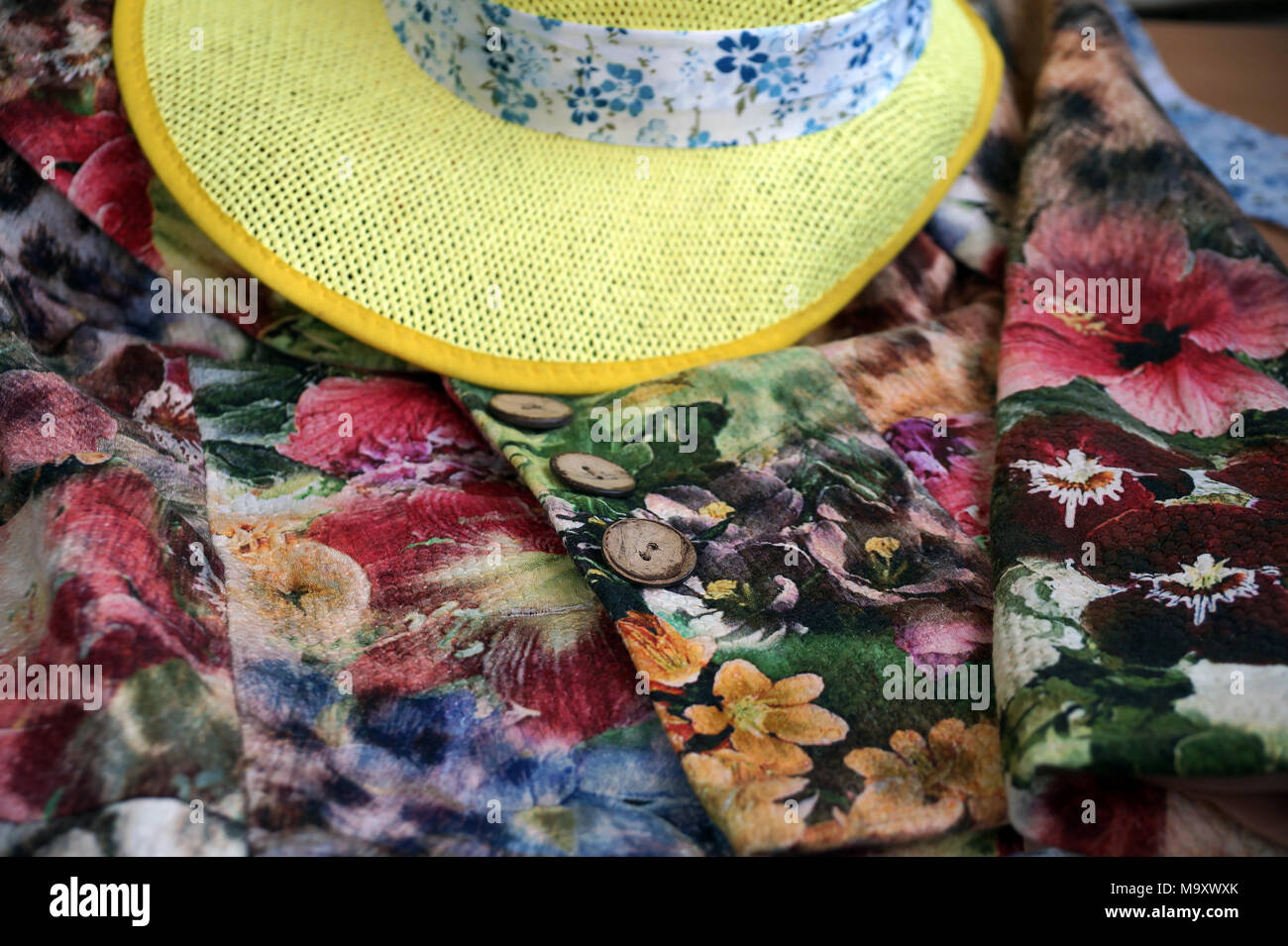 Motley cardigan and yellow hat with a tape - Stock Image