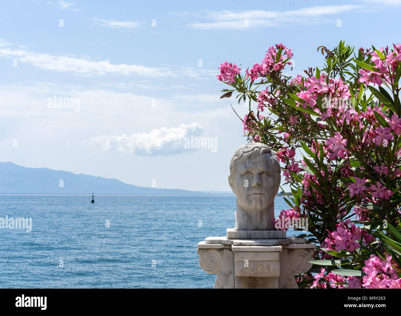 nice statue in Sarande, Albania in front of a beautiful sea panorama, with some flowers next to it - Stock Image