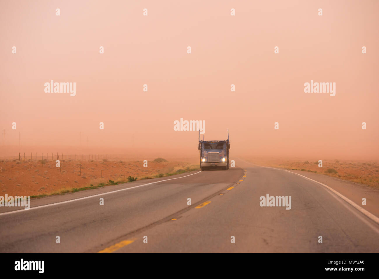 Big rig American bonnet car hauler semi truck with turn on headlight running on the road with very poor visibility in the red sand dust during huge sa Stock Photo