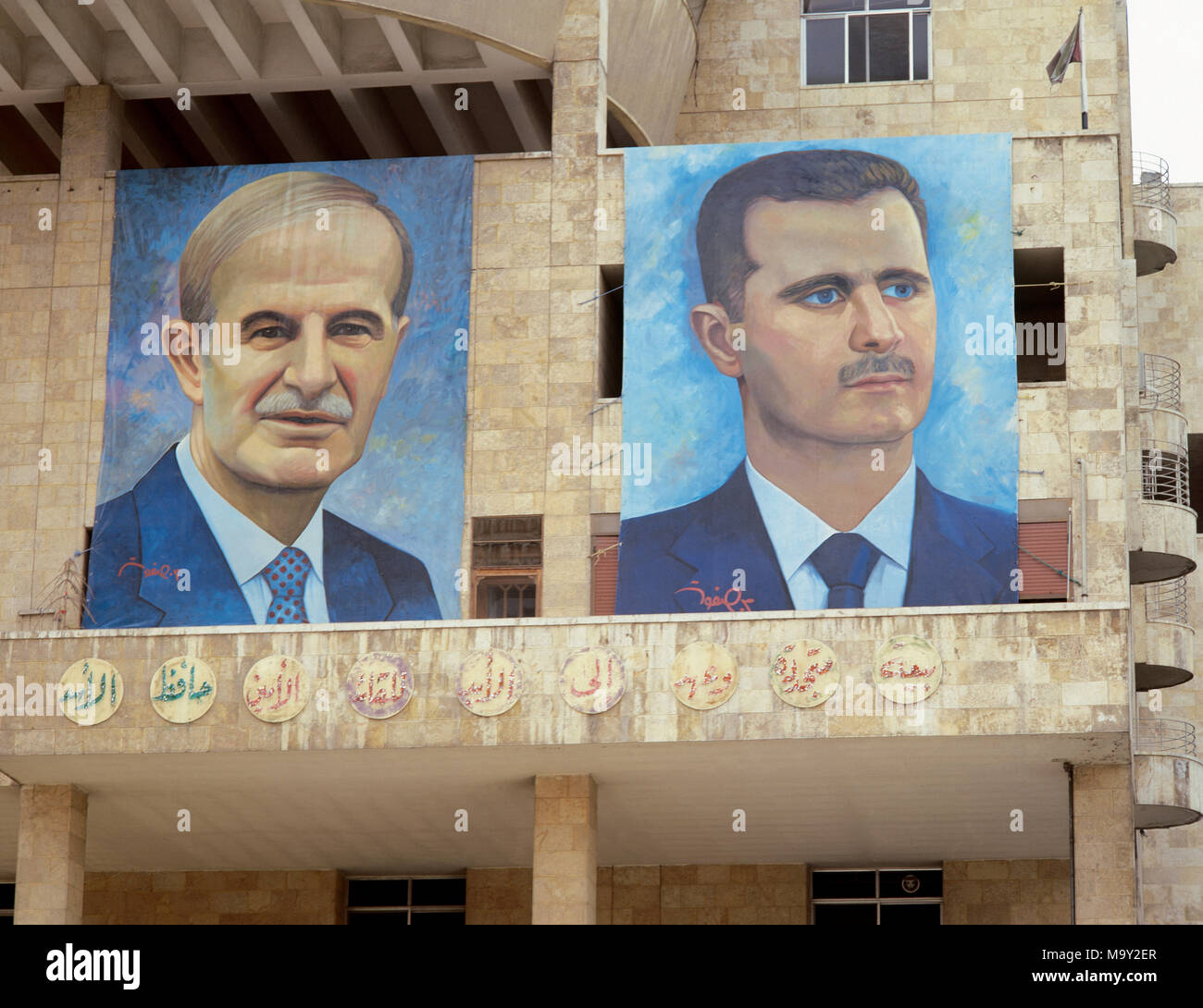 Presidents of Syria. Left: Hafez al-Asad (1930-2000), right: Basahr al-Assad (1965). Large portraits. Hamidie souk. Damascus. Picture took before the Civil War. - Stock Image
