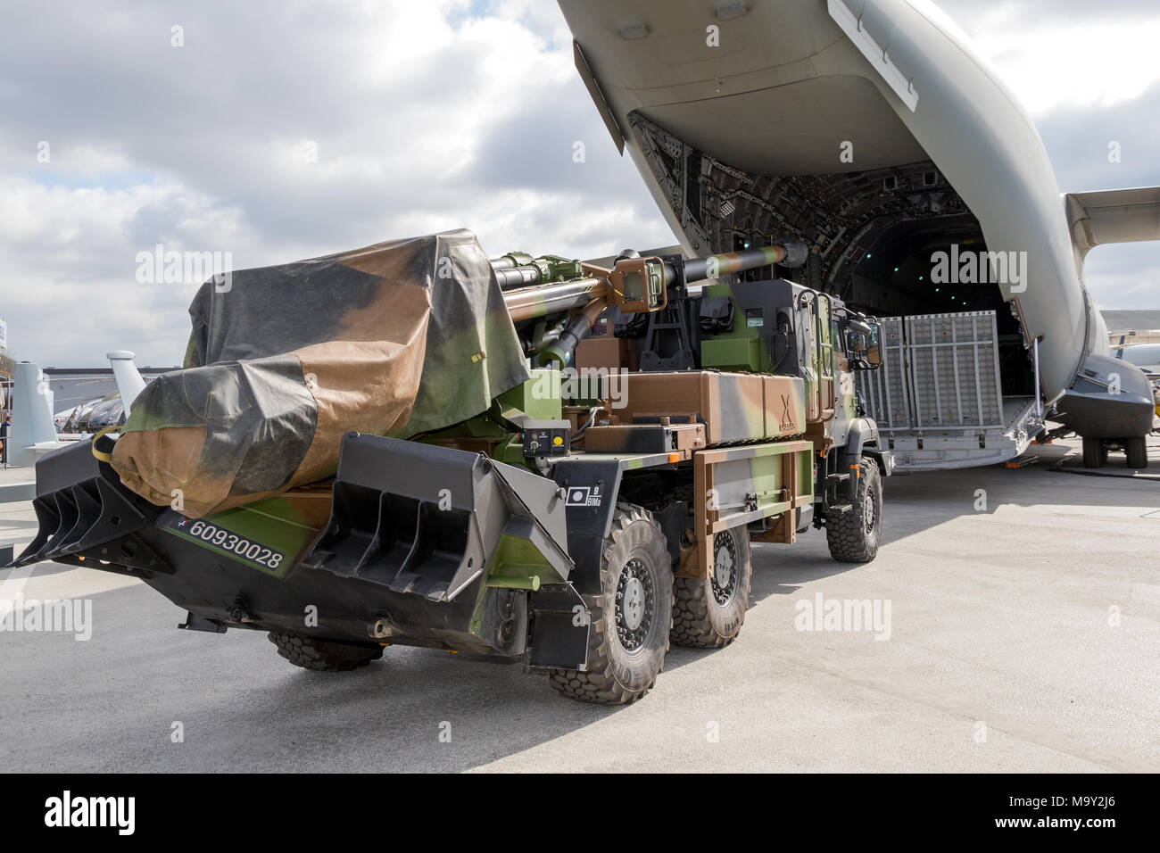 PARIS, FRANCE - JUN 23, 2017: Artillery truck in front of the loading door of an Airbus A400M military transport plane on display at the Paris Air Sho - Stock Image