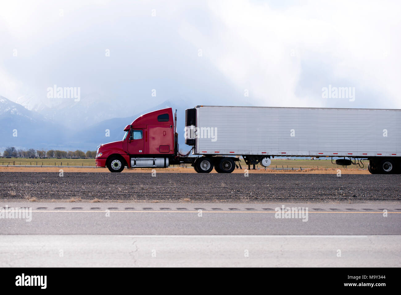 Side view of bright red big rig semi truck fleet transporting cargo in long refer semi