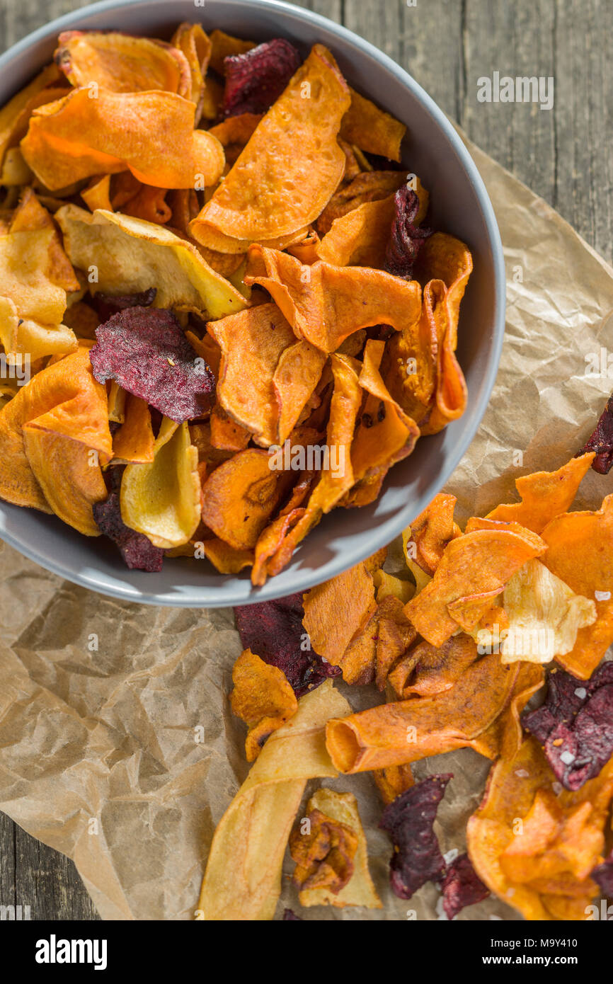 Mixed fried vegetable chips on old table. - Stock Image