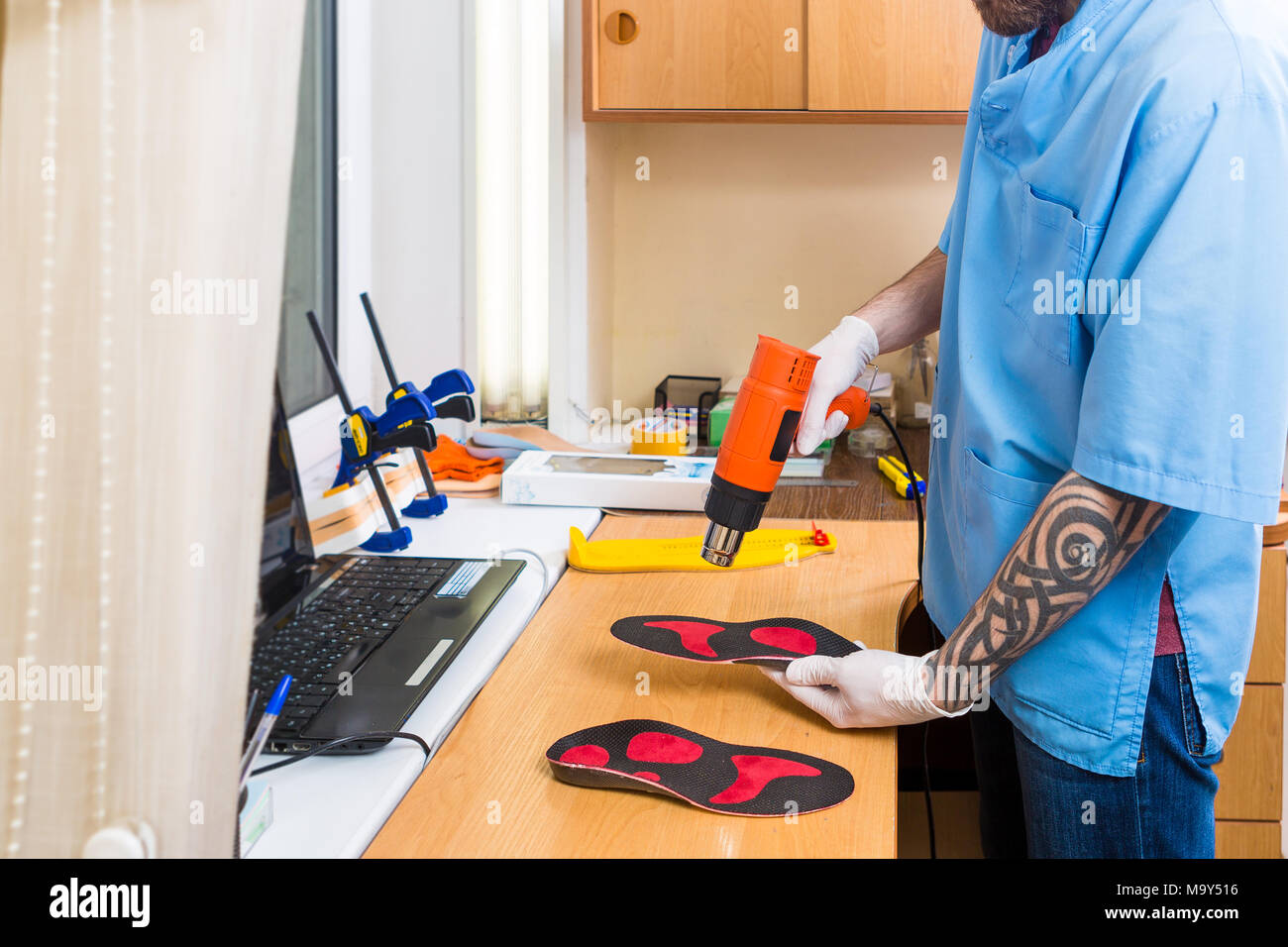 closeup Hands of young man with tattoo in workshop dressed in blue uniform make individual orthopedic insoles. The instrument uses hairdryer to heat and deform. Theme of small business and medicine - Stock Image