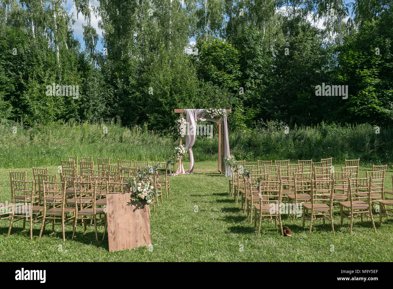 Beautiful setting for outdoors wedding ceremony waiting for bride and groom and guests. Wooden chairs decorated with flowers, are in the zone of the wedding ceremony in a forest - Stock Image