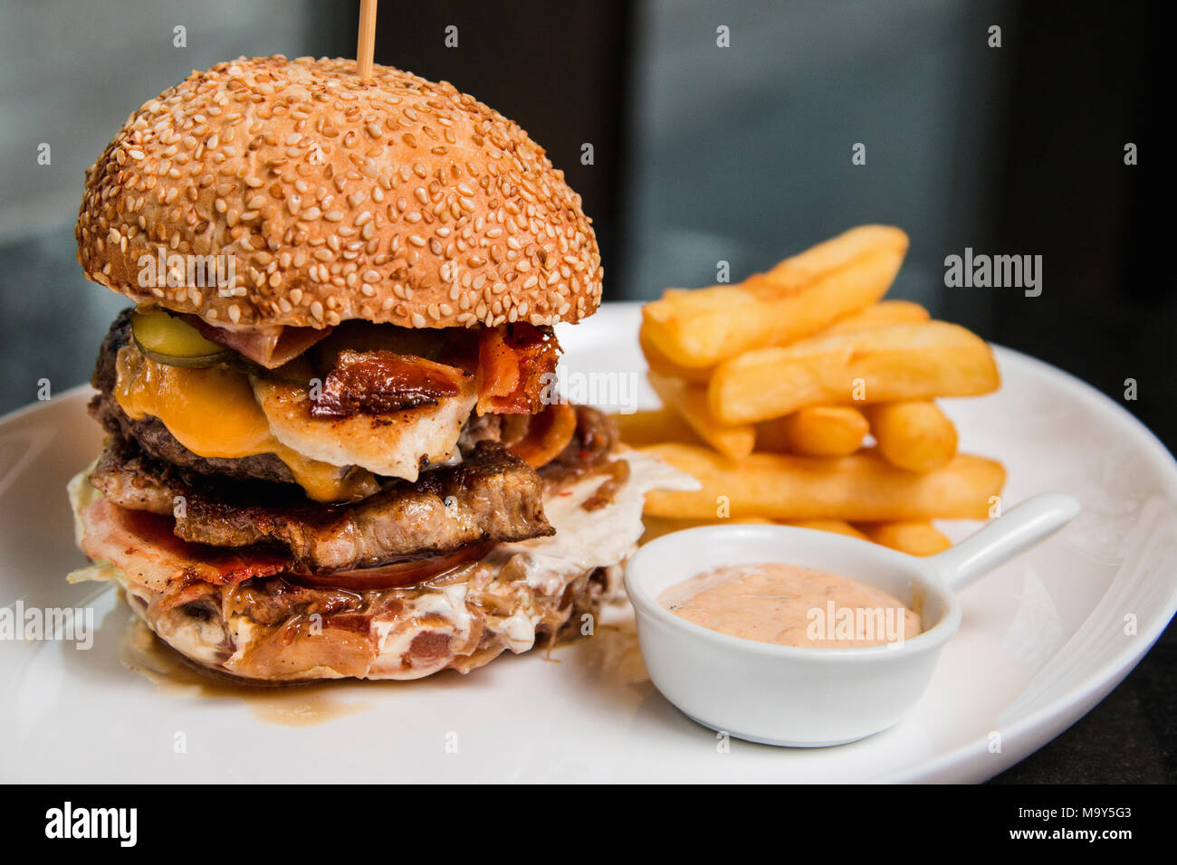 Close up of a delicious burger with sauce and fries - Stock Image