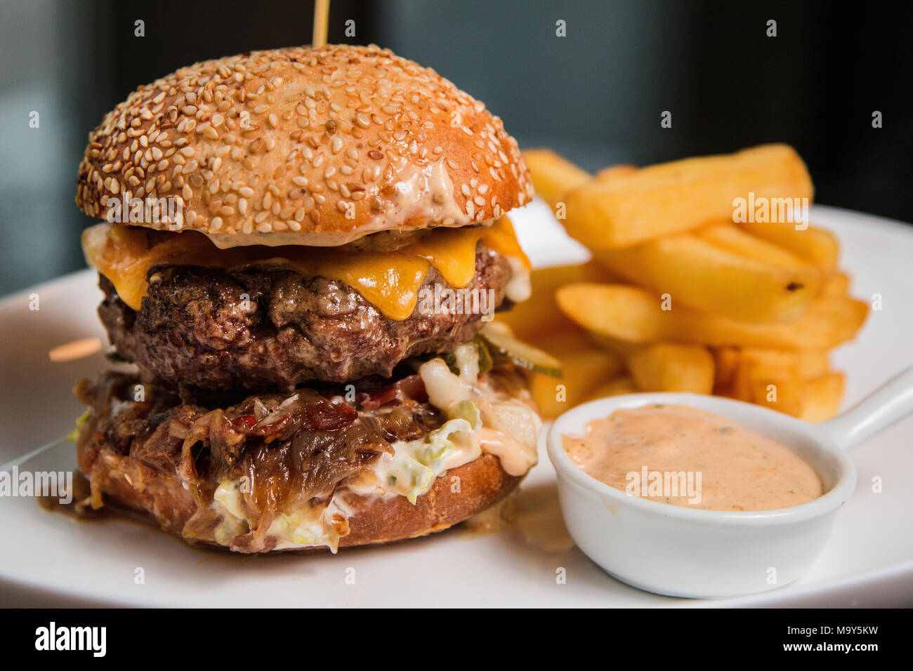 Close up of a tasty burger with sauce and fries - Stock Image