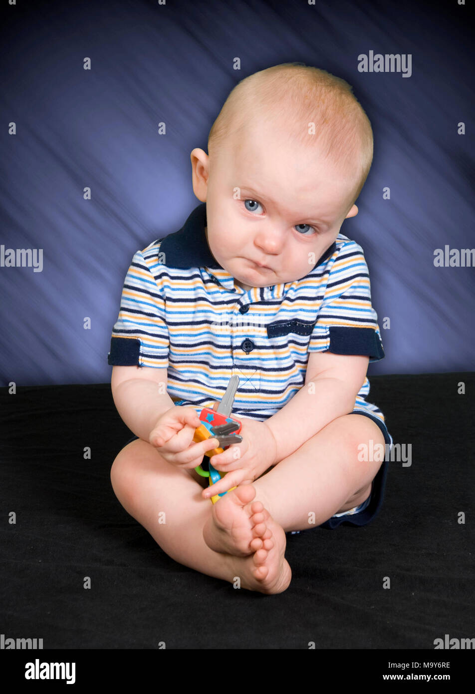 Sad 10 Month old Baby Boy playing with toy - Stock Image