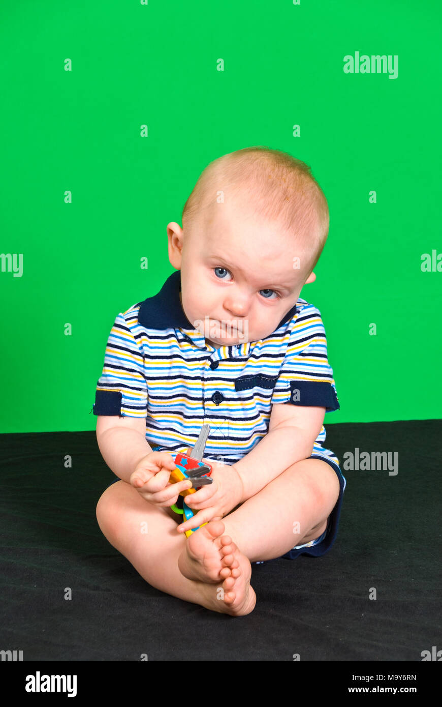Sad 10 Month old Baby Boy on Green Screen playing with toy - Stock Image