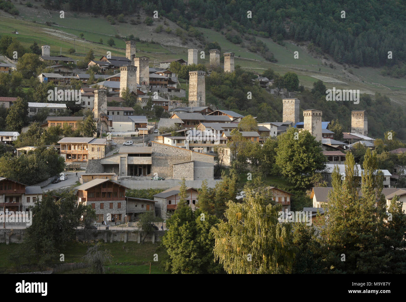 Historic tower houses amidst modern buildings on a hillside in Mestia, Svaneti region of the Caucasus, Georgia - Stock Image