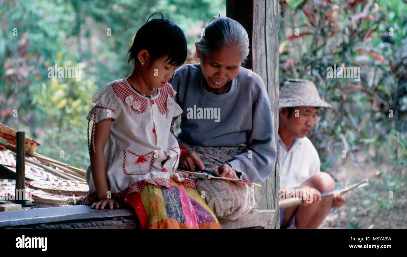 An indigenous Shan woman teaches her granddaughter how to make a bamboo fan in their small village near Hsipaw, Shan State, Burma (Myanmar). - Stock Image