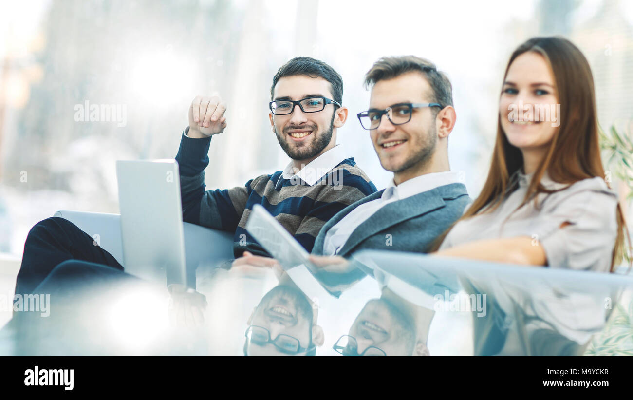 success concept in business - a professional business team sitting near the transparent table on a light background. - Stock Image
