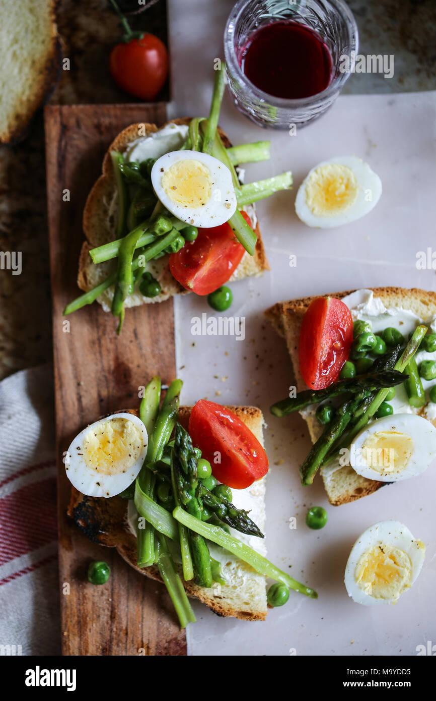 Quail eggs, peas and asparagus crostini - Stock Image