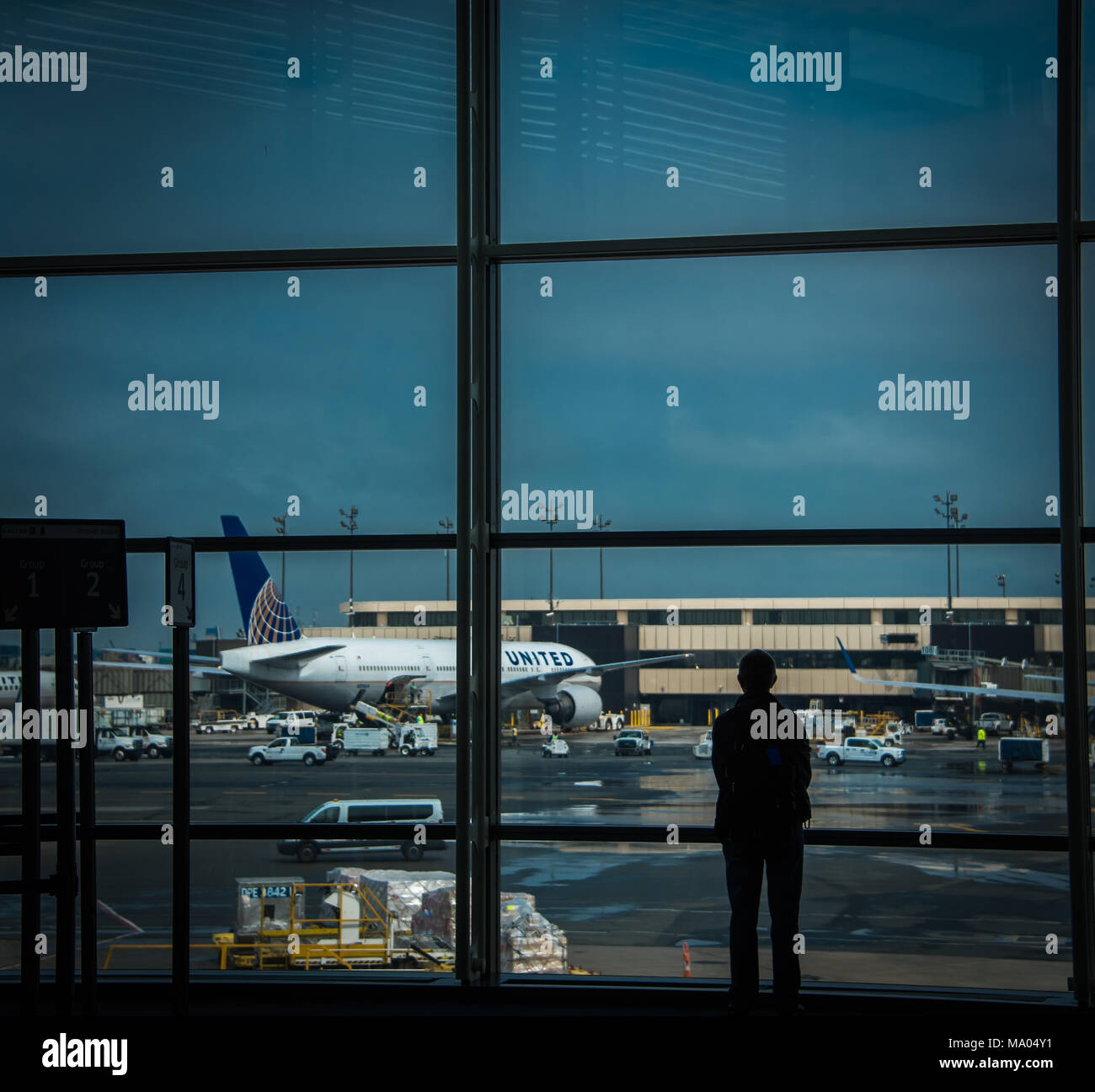 Silhouete of man looking at planes at airport - Stock Image