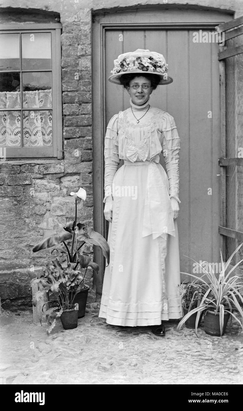 Young woman dressed as a bridesmaid in late Victorian England. She is wearing round spectacles, and is dressed entirely in white, with an elaborate white flowered hat. Stock Photo