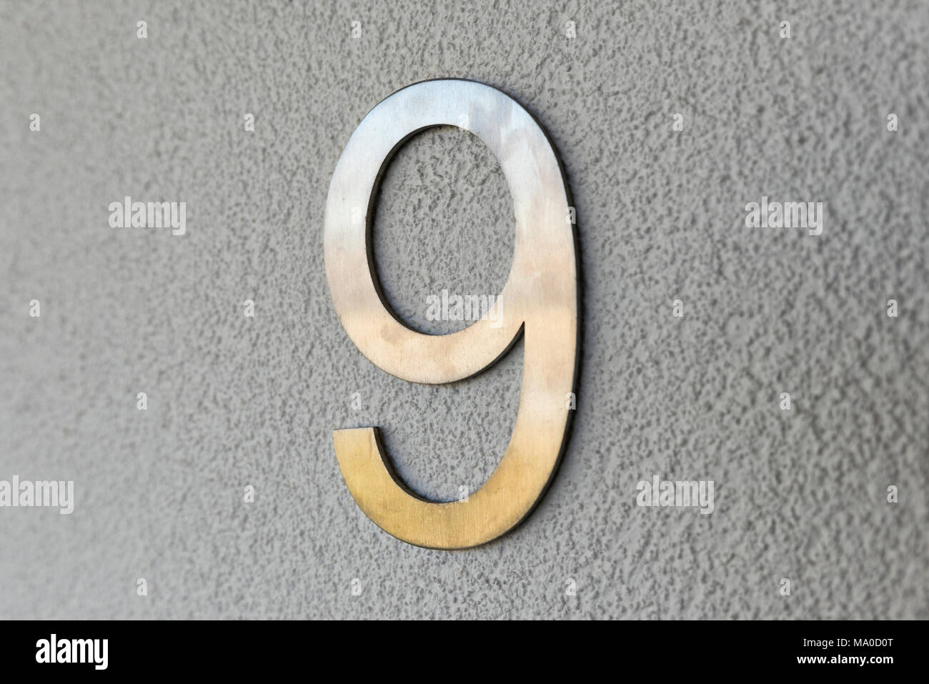 A stainless steel number nine attached to the grey wall of a home to show the properties address. - Stock Image