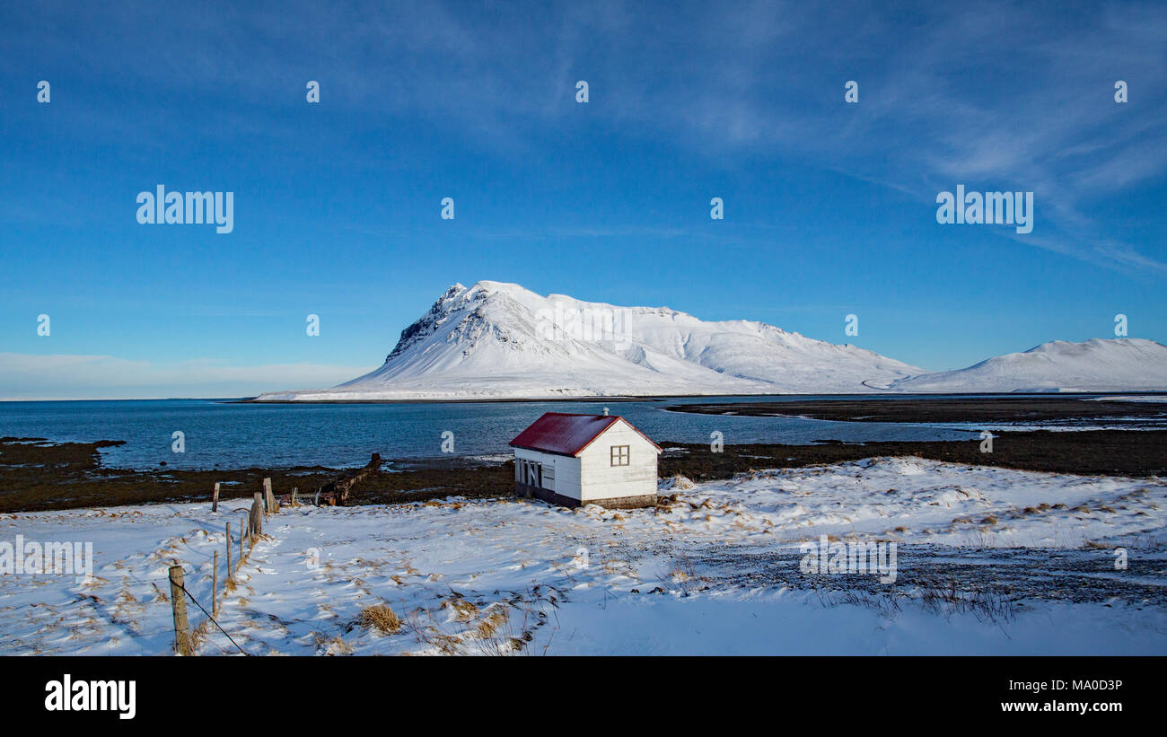 A boathouse with a red roof at the edge of the sea in the middle of a harsh winter on Iceland. 2015 was a particularly harsh winter on Iceland. - Stock Image