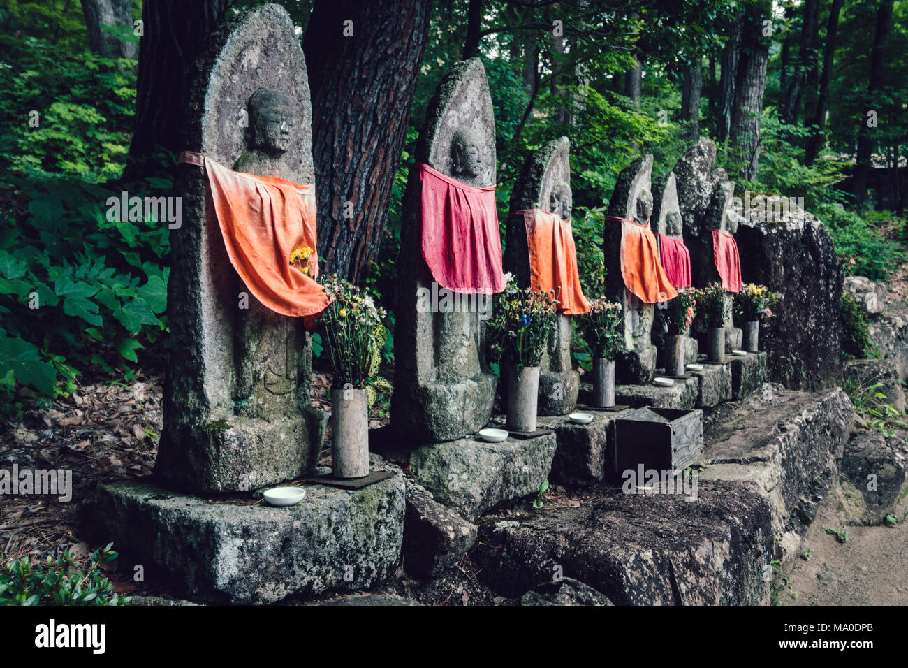 Hida Folk Village (Takayama, Japan) - Jizō statues wearing Red Bibs - Stock Image