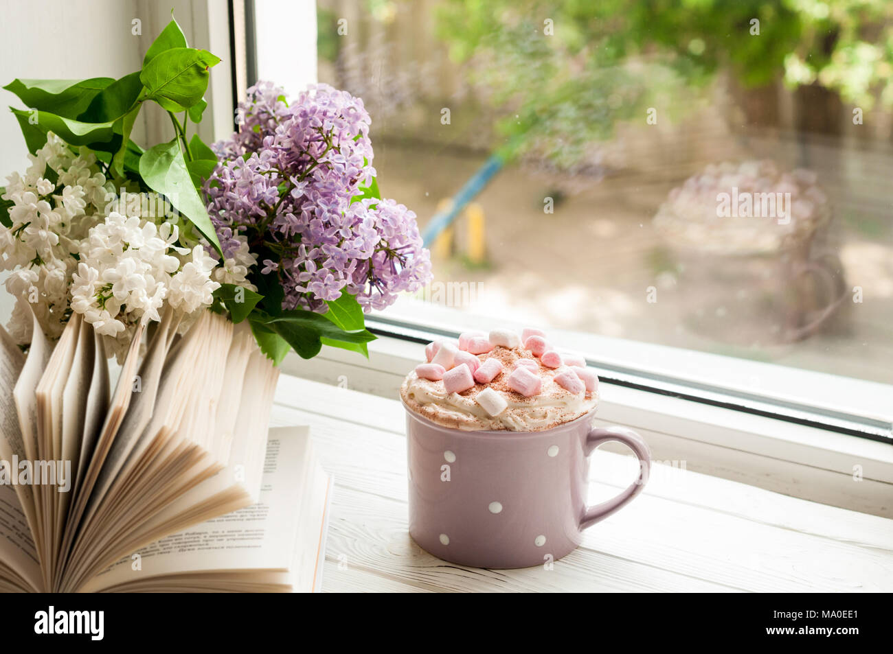 Coffee cup with marshmallow, open book and flowers bouquet on window ...